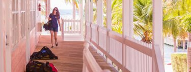 little cayman girl walking rooms bags 1060x403 min